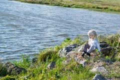 Blonder durchdachter Junge, der in einer Flussbank auf Felsen sitzt Lizenzfreie Stockfotos