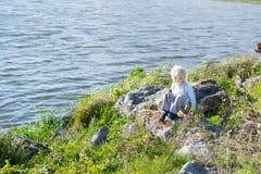 Blonder durchdachter Junge, der in einer Flussbank auf Felsen sitzt Lizenzfreie Stockfotografie