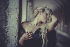 Blonder Engel des sexy Zaubers, junge Frau mit schwarzen Flügeln, Herbst Stockfotografie