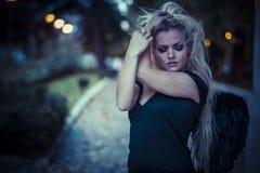 Blonder Engel, junge Frau mit schwarzen Flügeln, Herbstszene Lizenzfreies Stockfoto
