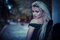 Blonder Engel, junge Frau mit schwarzen Flügeln, Herbstszene Lizenzfreies Stockbild