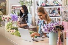 Blonder Florist, der Laptop während Afroamerikanerkollege arbeitet mit Blumen hinten verwendet Lizenzfreie Stockbilder