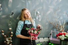 Blonder Florist, der zur Kamera lächelt und bei der Arbeit stillsteht Stockfoto