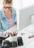 Blonder Fotograf, der über Kontaktblatt ihrem Schreibtisch betrachtet Stockfotos