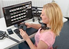 Blonder Fotograf der jungen Frau, der mit Computer und Grafik arbeitet Lizenzfreie Stockfotos