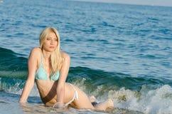 Blonder Frauenabnutzungsbikini, der im Meer liegt Lizenzfreie Stockbilder