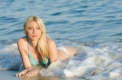 Blonder Frauenabnutzungsbikini, der im Meer liegt Lizenzfreie Stockfotos
