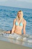 Blonder Frauenabnutzungsbikini, der im Meer liegt Lizenzfreies Stockfoto