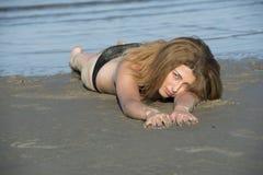 Blonder Frauenabnutzungsschwarzbikini, der auf dem Strand liegt Lizenzfreies Stockfoto