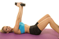 Blonder Frauenblau-Sport-BH legen auf das hintere oben schauende Gewicht Lizenzfreie Stockfotos