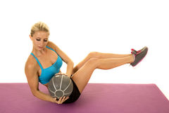 Blonder Frauenblau-Sport-BH setzen sich Balltorsionsblick hin Stockbild