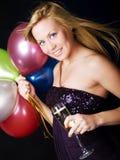 Blonder Frauenholding Ballons- und champagnchampagner Lizenzfreie Stockbilder
