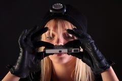 Blonder Frauenkatzeeinbrecher, der eine Spionkamera verwendet Stockfoto
