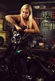 Blonder Frauenmechaniker, der ein Motorrad repariert Lizenzfreie Stockbilder