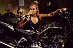Blonder Frauenmechaniker, der ein Motorrad repariert Stockbilder