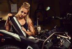 Blonder Frauenmechaniker, der einen Schalldämpfer hält Lizenzfreies Stockfoto