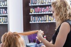 Blonder Friseur, der einen Haarschnitt für junge Frau macht Stockbild