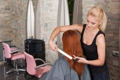 Blonder Friseur, der rotes Haar mit Haareisen geraderichtet Stockfotos