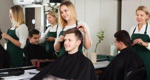 Blonder Friseurumhüllungsjugendlicher im Friseur Stockfotografie