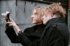 Blonder gelockter Kerl und das gleiche M?dchen Fotos von selbst machen und Fotos herum machen lizenzfreie stockfotografie