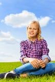 Blonder gelockter Mädchenabschluß herauf die Ansicht, die auf Gras sitzt Lizenzfreie Stockfotos