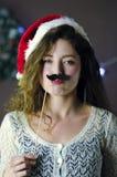 Blonder gelockter schöner lächelnder Mädchen tragender Weihnachtshut, der Spaßpapierschnurrbart auf Weihnachtsdekorationshintergr Stockfotografie