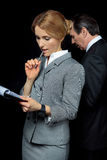 Blonder Geschäftsfraubehälter und Betrachten von Papieren während Geschäftsmann, der hinten steht Stockfoto