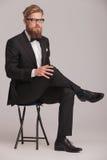 Blonder Geschäftsmann, der auf einem Schemel sitzt Stockfotos