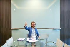 Blonder Geschäftsmann, der ein Projekt auf leerem Glasbrett darstellt Lizenzfreie Stockfotos