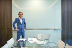 Blonder Geschäftsmann, der ein Projekt auf leerem Glasbrett darstellt Stockfoto