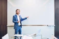 Blonder Geschäftsmann, der ein Projekt auf leerem Glasbrett darstellt Lizenzfreies Stockbild