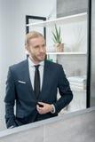 Blonder Geschäftsmann in der Klage, die im Spiegel im Badezimmer schaut Lizenzfreie Stockfotos