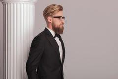Blonder Geschäftsmann, der nahe einer weißen Spalte aufwirft Stockfoto