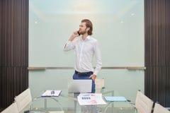 Blonder Geschäftsmann, der am Telefon mit leerem Glasbrett spricht Stockfoto