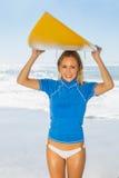 Blonder glücklicher Surfer, der ihr Brett auf dem Strand hält Lizenzfreies Stockbild