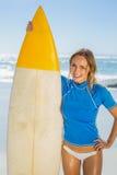 Blonder glücklicher Surfer, der ihr Brett auf dem Strand hält Lizenzfreie Stockfotos