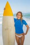 Blonder glücklicher Surfer, der ihr Brett auf dem Strand hält Stockfotos