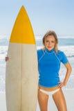 Blonder glücklicher Surfer, der ihr Brett auf dem Strand hält Stockbild
