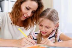 Blonder Griff des kleinen Mädchens in der Armbleistift-zeichnung etwas Stockfotografie
