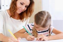 Blonder Griff des kleinen Mädchens in der Armbleistift-zeichnung etwas Stockfoto