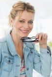 Blonder hübscher Designer, der die Kamera mit einem Lächeln betrachtet Lizenzfreie Stockbilder