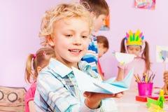 Blonder hübscher Junge zeigt Origami Stockbild