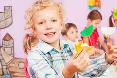 Blonder hübscher Junge zeigt Origamihandwerk in der Klasse Stockfoto
