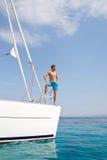 Blonder hübscher junger Mann, der auf Segelboot aufwirft. Lizenzfreie Stockfotos