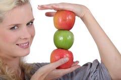 Blonder haltener Stapel von Äpfeln Lizenzfreie Stockfotografie
