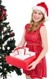 Blonder haltener Stapel von Geschenken mit Weihnachtsbaum hinter ihr Stockfotografie