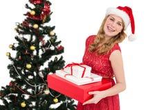 Blonder haltener Stapel von Geschenken mit Weihnachtsbaum hinter ihr Stockbilder