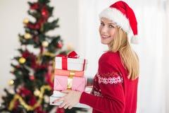 Blonder haltener Stapel von Geschenken vor dem Weihnachtsbaum Stockfoto