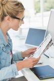 Blonder Herausgeber, der über Kontaktblatt ihrem Schreibtisch betrachtet Stockfotos