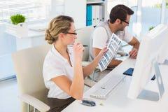 Blonder Herausgeber, der über Kontaktblatt ihrem Schreibtisch betrachtet Stockbilder